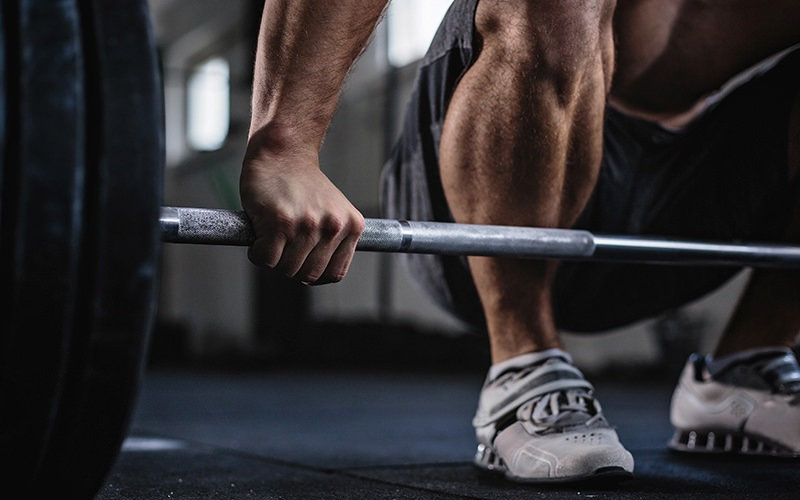 A person lifting a barbell in a modern style gym